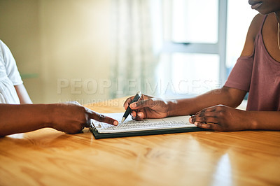 Buy stock photo Cropped shot of two people going over paperwork at home
