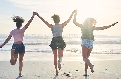 Buy stock photo Shot of three friends spending the day at the beach