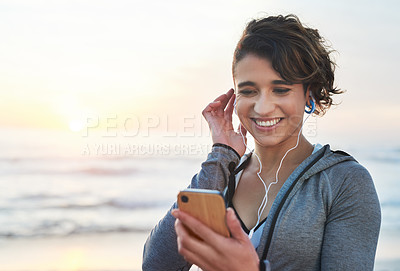 Buy stock photo Shot of a woman using her cellphone while out for a run