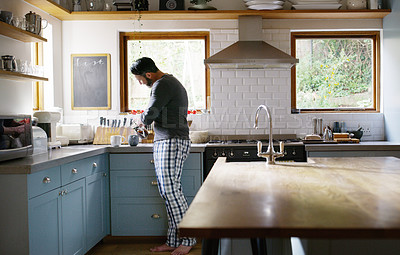 Buy stock photo Shot of a man making two cups of coffee in the kitchen at home