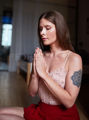 Buy stock photo Shot of an attractive young woman sitting down and meditating inside her apartment