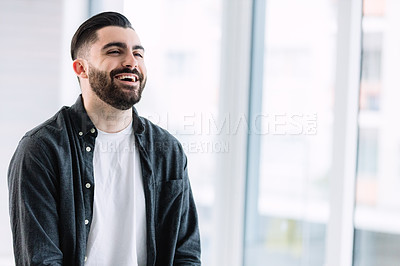 Buy stock photo Shot of a young businessman laughing in an office