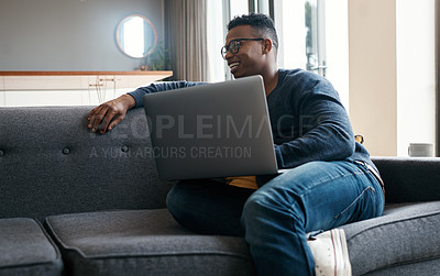 Buy stock photo Cropped shot of a young man using a laptop while relaxing on the sofa at home