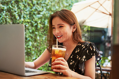 Buy stock photo Shot of an attractive young woman having drinks and using her laptop while relaxing at an outdoor cafe