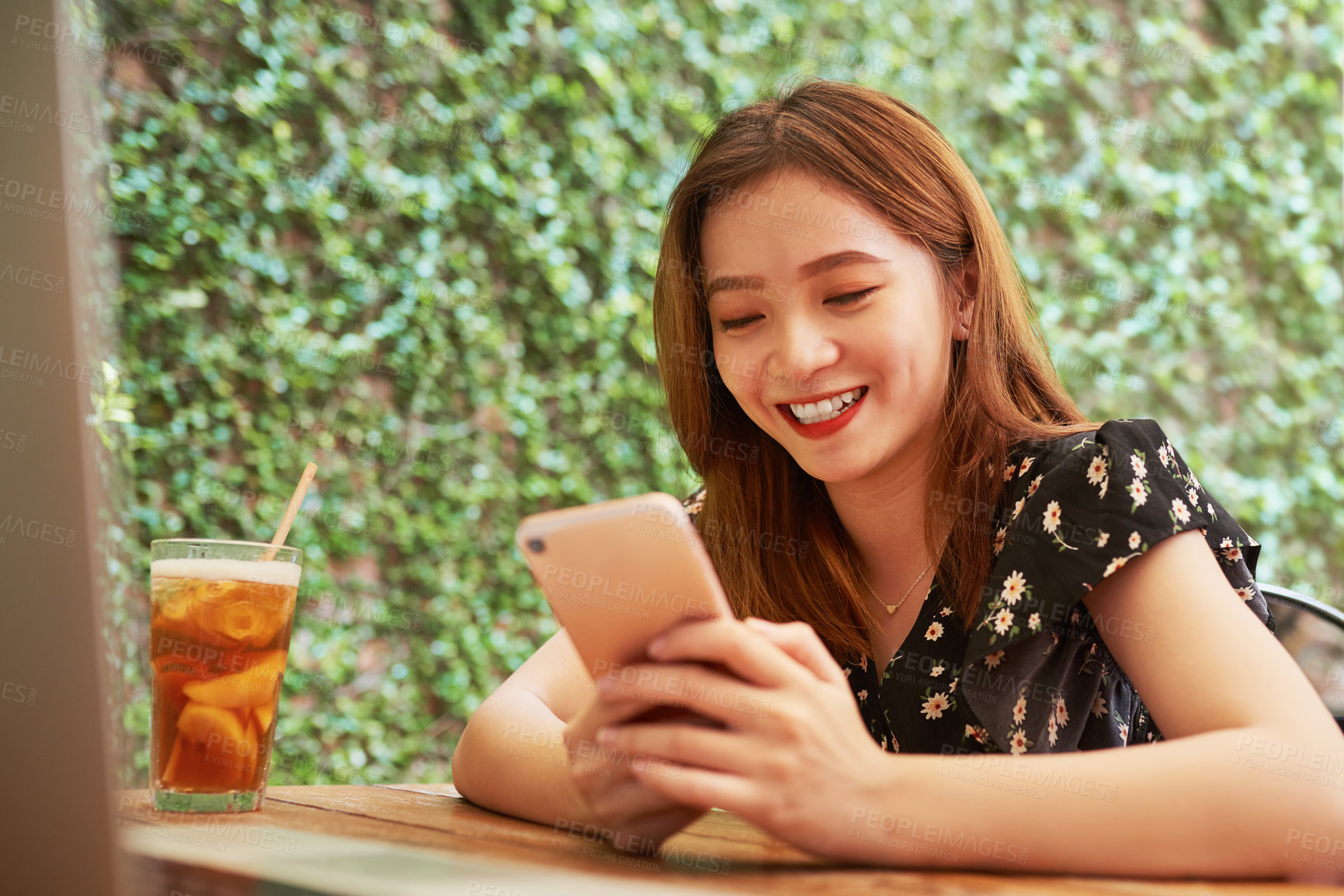 Buy stock photo Shot of an attractive young woman using her laptop and cellphone while relaxing at an outdoor cafe