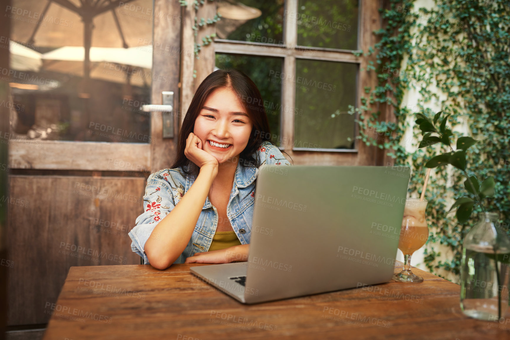 Buy stock photo Portrait of an attractive young woman having drinks and using her laptop while relaxing at an outdoor cafe