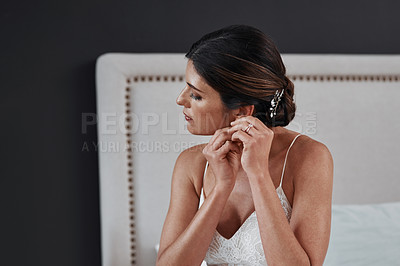 Buy stock photo Cropped shot of an attractive young bride putting in her earrings while getting dressed for her wedding ceremony