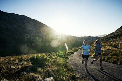 Buy stock photo Shot of two determined young women jogging on a open road up in a mountain outside during the day