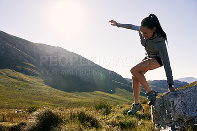 Buy stock photo Shot of a determined young woman carefully climbing down a rock on a mountain trail outside during the day