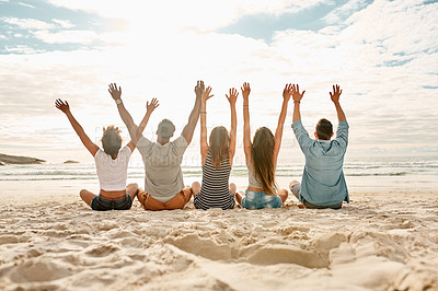 Buy stock photo Rearview shot of a group of happy young friends cheering while watching the sunset at the beach