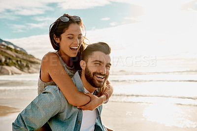 Buy stock photo Shot of a happy young couple enjoying a piggyback ride on the beach