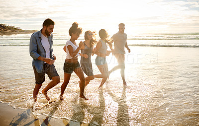 Buy stock photo Shot of a group of happy young friends running along the water's edge at the beach
