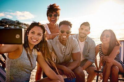 Buy stock photo Shot of a group of happy young friends taking selfies together at the beach