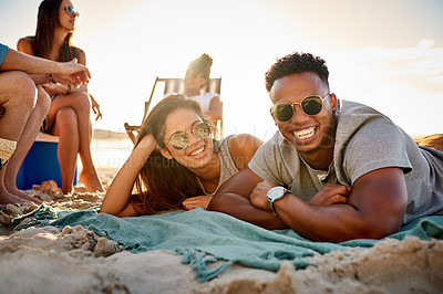 Buy stock photo Shot of a young man and woman hanging out with friends at the beach