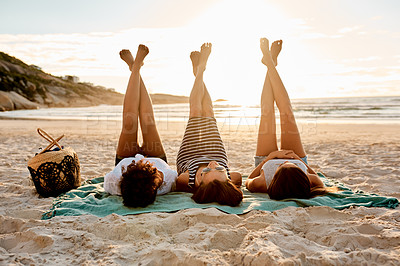 Buy stock photo Shot of a group of young women relaxing together with their legs up at the beach