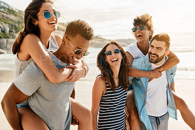 Buy stock photo Shot of a group of happy young friends enjoying piggyback ride at the beach