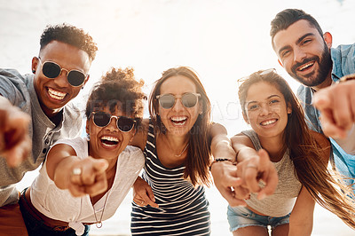 Buy stock photo Portrait of a group of happy young friends pointing while enjoying a summer's day at the beach