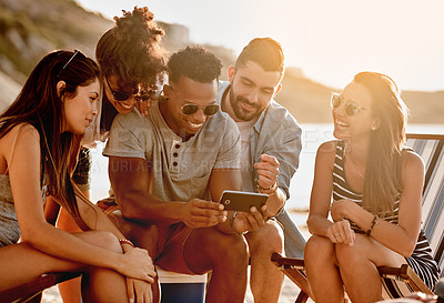 Buy stock photo Shot of a group of happy young friends using a smartphone together at the beach