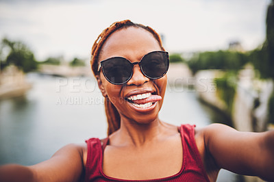 Buy stock photo Shot of a young woman taking fun selfies while touring the city of Paris
