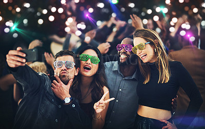 Buy stock photo Cropped shot of a diverse group of young friends taking a selfie together at a party at night