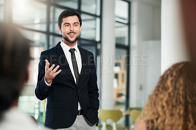 Buy stock photo Shot of a handsome young businessman giving a speech and explaining his ideas at a business conference
