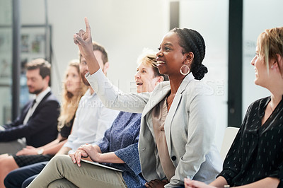 Buy stock photo Shot of an attractive young businesswoman raising her hand to ask a question at a business conference