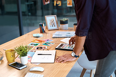 Buy stock photo Cropped shot of an unrecognizable businessman standing alone in his office and using a tablet to view colour swatches
