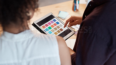 Buy stock photo Rearview shot of two unrecognizable business colleagues standing together and using a tablet to view colour swatches