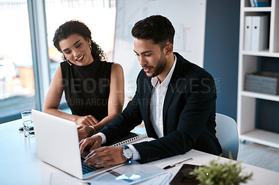 Buy stock photo Cropped shot of two young business colleagues sitting together and using a laptop in the office