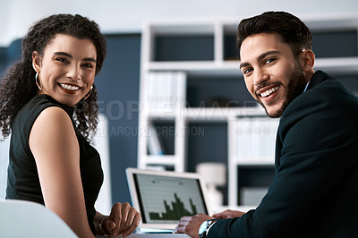 Buy stock photo Cropped portrait of two young businesspeople sitting together and having a discussion while using a laptop in the office