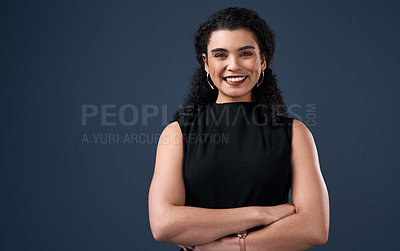 Buy stock photo Cropped portrait of an attractive young businesswoman standing against a gray background alone with her arms folded