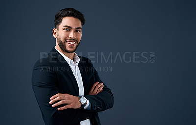 Buy stock photo Cropped portrait of a handsome young businessman standing against a gray background alone with his arms folded