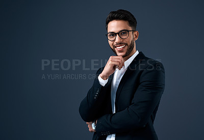 Buy stock photo Cropped portrait of a handsome young businessman wearing spectacles and standing alone against a gray background