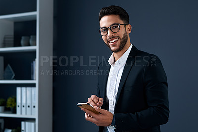 Buy stock photo Cropped portrait of a handsome young businessman standing alone against a gray studio background and texting on his cellphone