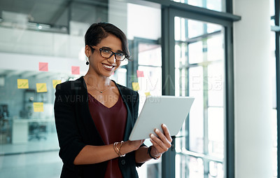 Buy stock photo Cropped portrait of an attractive young businesswoman standing alone in her office and working on a tablet