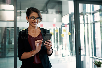 Buy stock photo Cropped shot of an attractive young businesswoman standing alone in her office and texting on her cellphone