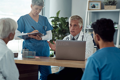 Buy stock photo Cropped shot of a handsome mature male doctor having a discussion with his colleagues during a meeting in his office