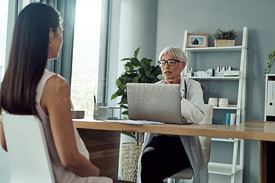 Buy stock photo Cropped shot of an attractive mature female doctor using a laptop while having a discussion  with her pregnant patient in her office