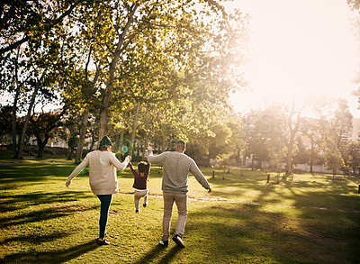 Buy stock photo Rearview shot of a couple having fun with their little son at the park