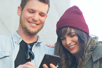 Buy stock photo Cropped shot of an affectionate young couple using a cellphone together outdoors