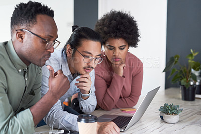Buy stock photo Shot of a group of young businesspeople using a laptop in a modern office