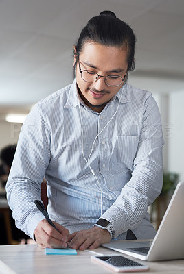Buy stock photo Shot of a young businessman using a laptop and making notes at his desk in a modern office