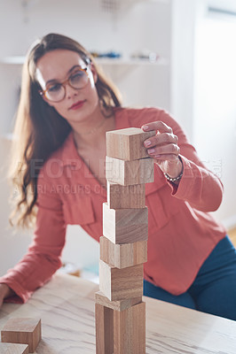 Buy stock photo Shot of a young businesswoman working with wooden building blocks in a modern office