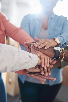 Buy stock photo Cropped shot of a group of young businesspeople joining hands in solidarity in a modern office