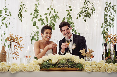 Buy stock photo Shot of a happy young couple having wine together at their wedding reception
