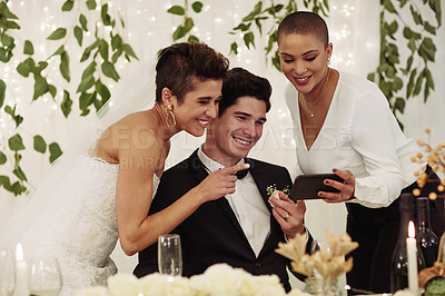 Buy stock photo Shot of a happy young couple using a smartphone with a friend at their wedding reception