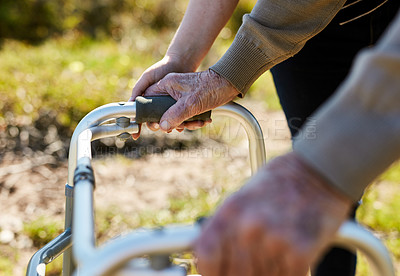 Buy stock photo Cropped shot of an unrecognizable senior man talking a stroll outdoors with the help of his nurse and mobility walker