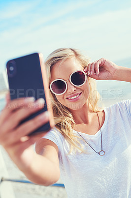 Buy stock photo Cropped shot of a young woman taking a selfie while spending the day by the sea