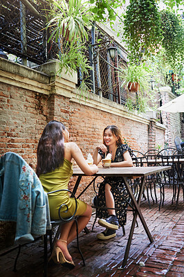 Buy stock photo Full length shot of two attractive young women having drinks and enjoying themselves at an outdoor cafe