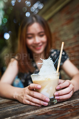 Buy stock photo Shot of an unrecognizable woman holding a glass of iced coffee at an outdoor cafe